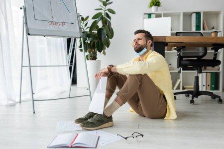 nachdenklicher Geschäftsmann, der auf dem Boden sitzt und in der Nähe von Papieren, Notizbuch und Flipchart mit Covid-19-Beschriftung und Infografiken wegschaut