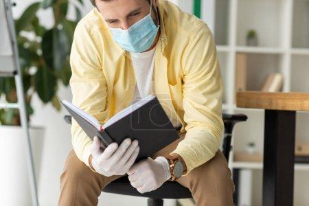 Geschäftsmann mit medizinischer Maske und Latexhandschuhen schaut im Büro in Notizbuch nach