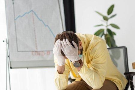 depressiver Geschäftsmann in Latex, der die Hände auf dem Kopf hält, während er neben Flipchart mit Covid-19-Aufschrift sitzt