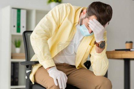 depressiver Geschäftsmann in Latexhandschuhen und medizinischer Maske, der im Büro die Hand auf die Stirn legt