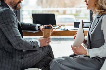 Photo pour Vue recadrée des hommes d'affaires avec café à emporter et dossier papier assis à table au bureau - image libre de droit