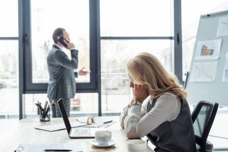 Photo pour Vue latérale d'une femme d'affaires assise à table avec un ordinateur portable et des papiers pendant que l'homme d'affaires parle sur son smartphone au bureau - image libre de droit