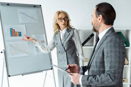 Photo pour Point de mire sélectif d'une femme d'affaires pointant sur des graphiques au tableau blanc près d'un homme d'affaires avec tableau à paire en fonction - image libre de droit