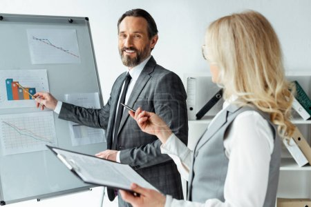 Selective focus of smiling businessman pointing on charts on whiteboard near businesswoman holding clipboard in office