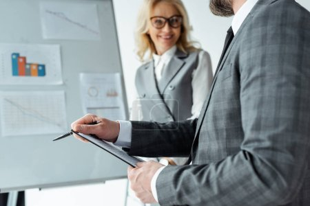 Selective focus of businessman holding clipboard near smiling businesswoman and whiteboard in office