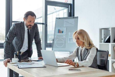 Photo pour Les gens d'affaires travaillant avec un ordinateur portable près des papiers et des tasses à café sur la table - image libre de droit