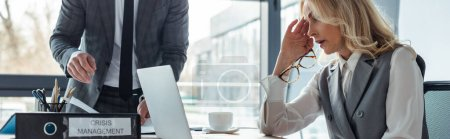 Photo for Panoramic shot of businesswoman looking at laptop near folder with crisis management and businessman in office - Royalty Free Image