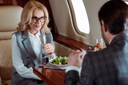 Photo for Selective focus of smiling businesswoman holding glass of champagne near businessman eating salad in plane - Royalty Free Image