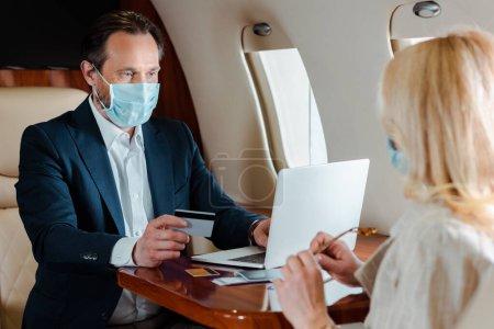 Foto de Enfoque selectivo de hombre de negocios en máscara médica con tarjeta de crédito y el uso de la computadora portátil cerca de la mujer de negocios en avión - Imagen libre de derechos