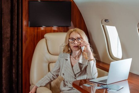 Businesswoman talking on smartphone near credit cards and laptop on table in plane
