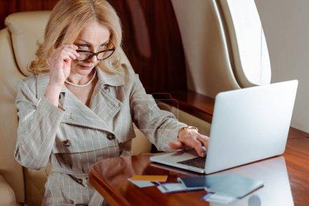 Foto de Enfoque selectivo de empresarias que utilizan laptop cerca de tarjetas de crédito y pasaportes con billetes de avión sobre la mesa en avión. - Imagen libre de derechos