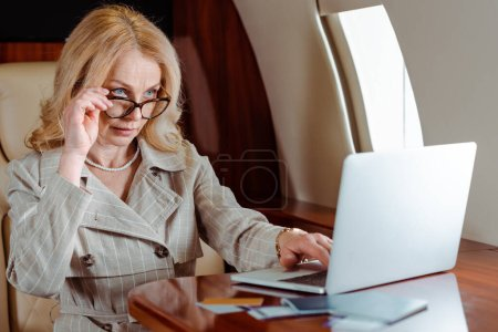 Photo for Selective focus of businesswoman holding eyeglasses while using laptop near credit cards and passports with air tickets on table in airplane - Royalty Free Image