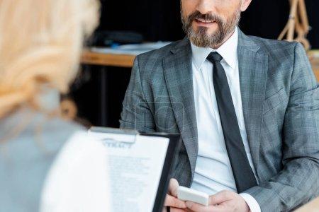 Photo pour Concentration sélective d'un homme d'affaires utilisant un téléphone intelligent près d'une femme d'affaires ayant un contrat au bureau - image libre de droit