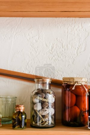 jar with canned tomatoes near small bottle with oil and herb