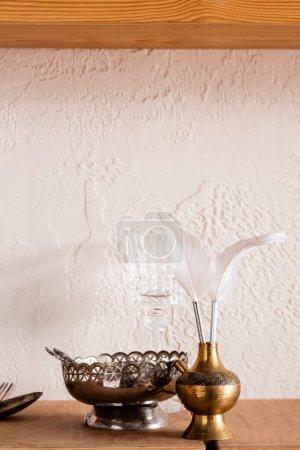 Photo pour Bol en argent près de plumes blanches dans un vase vintage - image libre de droit
