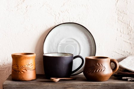wooden spoon near clay cups and plate in kitchen