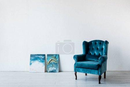Photo pour Fauteuil confortable près des peintures dans le salon - image libre de droit