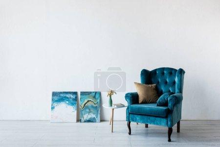 Photo pour Fauteuil confortable près du vase sur la table basse et des peintures dans le salon - image libre de droit