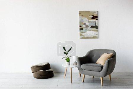 Photo pour Fauteuil confortable et oreiller près de la table basse avec des plantes vertes, lampe et peinture sur le mur dans le salon - image libre de droit
