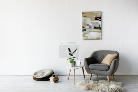 Photo for Comfortable armchair near coffee table with green plants, frame and painting on wall in modern living room - Royalty Free Image