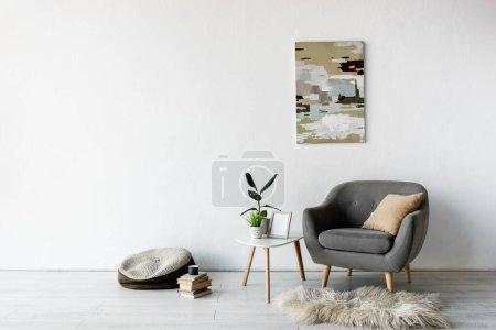 Photo pour Fauteuil confortable près de la table basse avec des plantes vertes, cadre et peinture sur mur dans le salon moderne - image libre de droit
