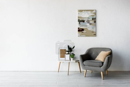Photo for Comfortable armchair near coffee table with green plants and frames in modern living room - Royalty Free Image