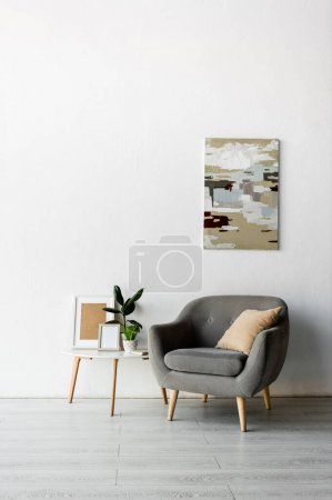 Photo for Grey armchair near coffee table with frames and green plants near painting on wall in modern living room - Royalty Free Image