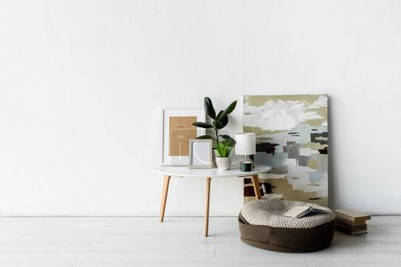 Photo for Green plants, frames and lamp on white coffee table near painting and books in modern apartment - Royalty Free Image
