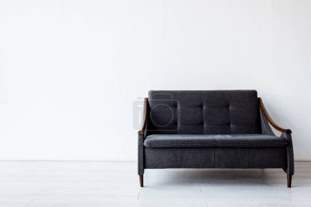 Photo for Modern dark sofa near while wall in living room - Royalty Free Image