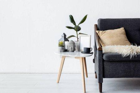 Photo pour Canapé moderne avec oreiller près de la table basse avec des plantes, lampe vintage et tasse dans le salon - image libre de droit