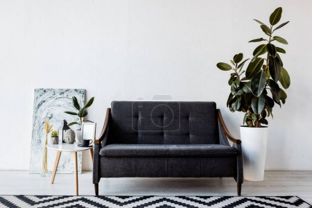 modern sofa near plants and coffee table with vintage lamp, head figurine and cup in living room