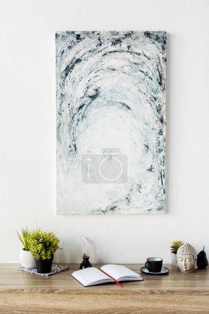 Photo pour Bloc-notes vierge près de plantes vertes, pot d'encre rétro, plume, figurine de tête et peinture sur mur - image libre de droit