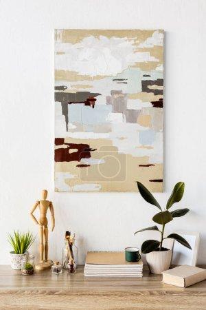 Photo pour Peinture sur mur près de la table avec mannequin en bois, plante, cahiers, livre, tasse, vase avec blé et cadre - image libre de droit