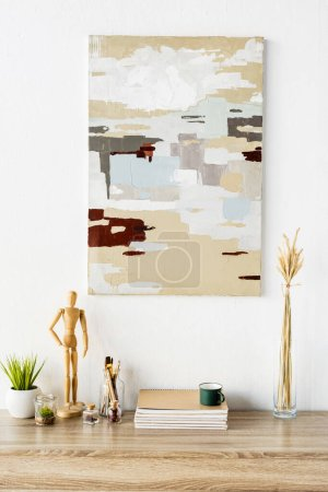 Foto de Pintura en la pared cerca de la mesa de madera con maniquí, planta, cuadernos, taza y jarrón con trigo - Imagen libre de derechos