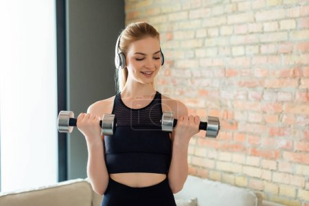 Photo for Cheerful and sportive girl in wireless headphones exercising with dumbbells at home - Royalty Free Image