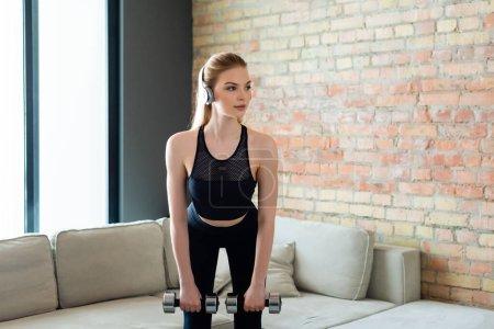 Photo pour Fille sportive dans les écouteurs sans fil exercice avec haltères à la maison - image libre de droit