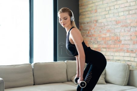 Photo for Sportive woman in wireless headphones exercising with dumbbells at home - Royalty Free Image