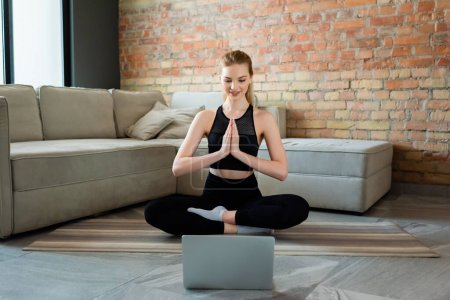 Photo for Happy sportswoman with praying hands watching online yoga exercise on laptop in living room - Royalty Free Image