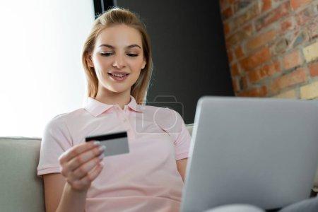 foyer sélectif de fille heureuse regardant la carte de crédit près de l'ordinateur portable