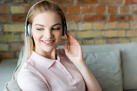 smiling woman touching wireless headphones at home