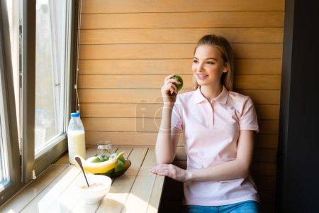 Foto de Mujer feliz sosteniendo manzana cerca de los copos de maíz en el tazón, botella con leche y frutas. - Imagen libre de derechos