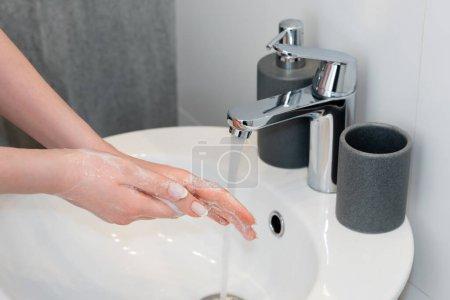 Photo pour Vue recadrée de femme se laver les mains savonneuses dans la salle de bain - image libre de droit