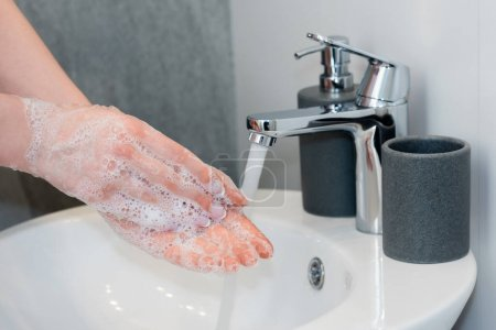 Photo for Cropped view of young woman washing soapy hands in bathroom - Royalty Free Image