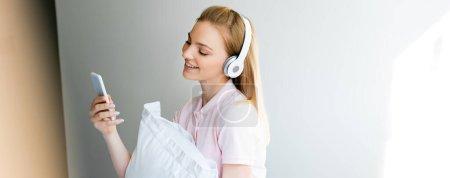 Photo pour Prise de vue panoramique d'une femme souriante dans un casque sans fil à l'aide d'un smartphone à la maison - image libre de droit