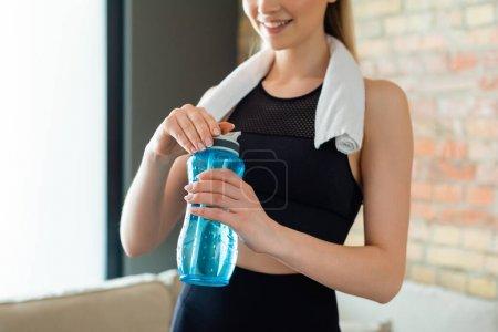 vista recortada de la deportista feliz sosteniendo botella de deportes en casa