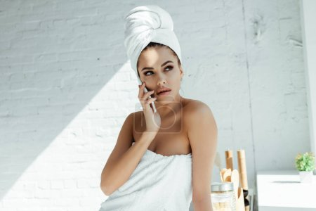 Photo for Beautiful young woman in towels talking on smartphone in kitchen - Royalty Free Image