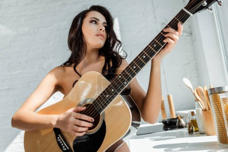 Photo for Beautiful naked woman playing acoustic guitar in kitchen - Royalty Free Image