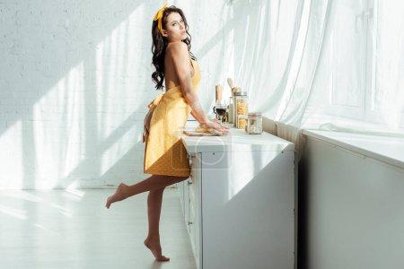Photo pour Vue latérale de la femme nue passionnée dans la pâte de cuisson tablier et regardant la caméra dans la cuisine - image libre de droit