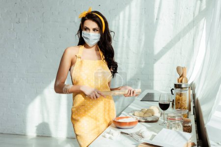 Photo for Nude girl in apron and medical mask holding rolling pin while cooking in kitchen - Royalty Free Image