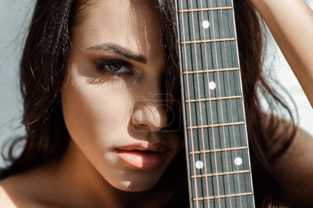 Photo for Beautiful woman looking at camera while holding acoustic guitar - Royalty Free Image